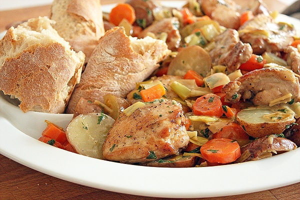 Tender and flavourful white wine braised chicken thighs are paired up with some super easy potatoes for a delicious meal any night of the week!