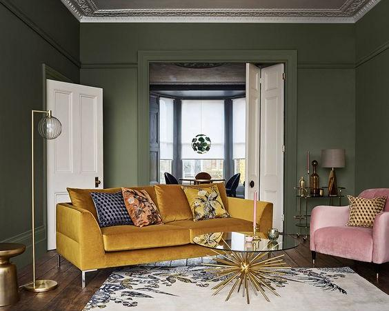 Living room with green walls, golden yellow sofa, pink chair and gold toned home accessories