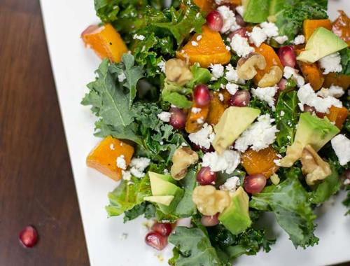 Wintry Kale Salad combines squash, pomegranates, feta cheese and avocado with a mustard balsamic ginger dressing for a healthy and flavorful salad.