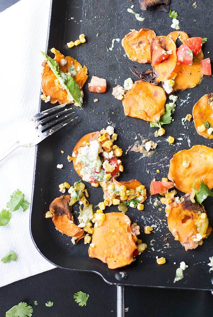 """Healthy Loaded Sweet Potato Nachos - sweet potato """"chips"""" topped with refried beans, roasted corn, queso fresco and a creamy cilantro and salsa verde sauce."""
