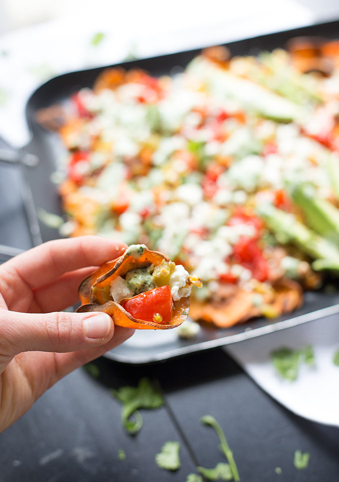 "Healthy Loaded Sweet Potato Nachos - sweet potato ""chips"" topped with refried beans, roasted corn, queso fresco and a creamy cilantro and salsa verde sauce."