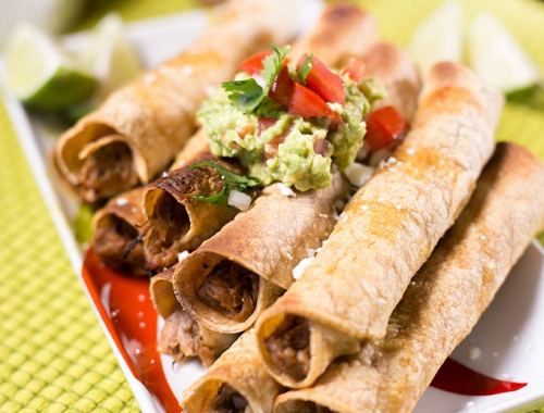 These Sweet Pork Taquitos are made with shredded pork cooked in a slow cooker and rolled into gluten free corn tortillas. Top with salsa and guacamole.
