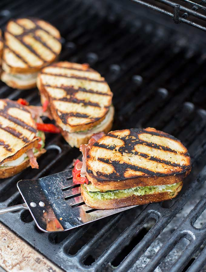 Grilled Italian Sandwiches - Fresh mozzarella and goat cheese, pesto, prosciutto, roasted peppers and zucchini nestled between two pieces of grilled garlic bread!
