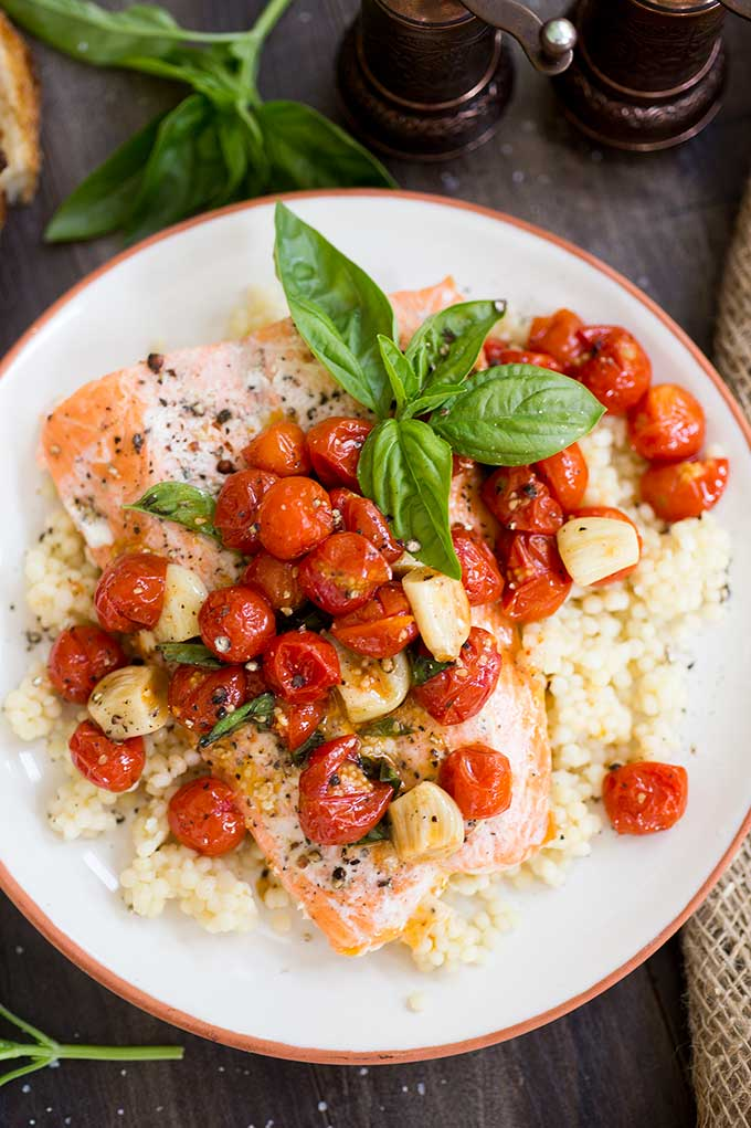One-Pan Roasted Salmon: Salmon filets share the same pan with tomatoes, garlic and basil for a super quick and easy, one-pan dinner!