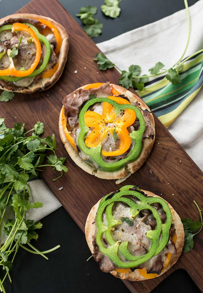 Philly Cheesesteak Pita Pizzas - peppers, onions, roast beef and pepperjack cheese piled high on a soft pita bread. Simple ingredients, minimal work and a husband-approved meal!