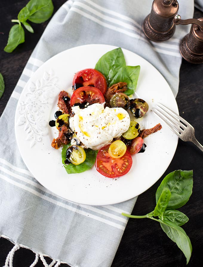 Triple Tomato and Burrata Salad: Sun-dried, cherry and roma tomatoes smothered in creamy burrata cheese, and topped with fresh basil leaves and basil olive oil!