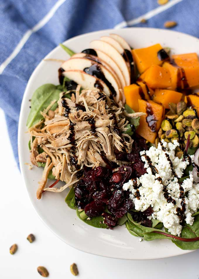 Kalua Pork Power Bowl - a giant bowl of mixed greens piled with shredded kalua pork, sweet potatoes, craisins, pistachios, crumbled goat cheese and shallots. Full of color and flavor!
