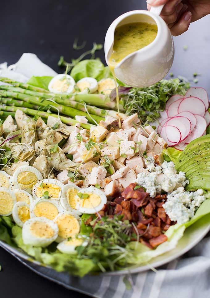 This Spring Cobb Salad recipe is a twist on the traditional cobb - butter lettuce piled high with hard-boiled eggs, bacon, blue cheese, asparagus, radish, grilled chicken, avocado and micro greens. Drizzled with a lemon basil vinaigrette for a bright and zesty flavor.