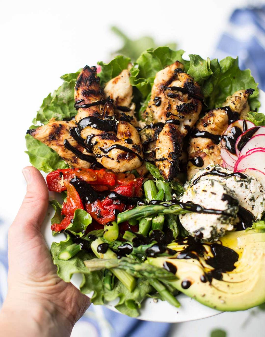 Lemon Chicken Spring Salad: Grilled lemon and garlic-marinated chicken on a bed of leafy greens, with spring radishes and asparagus, goat cheese, roasted peppers and avocado, drizzled with a sweet balsamic glaze.