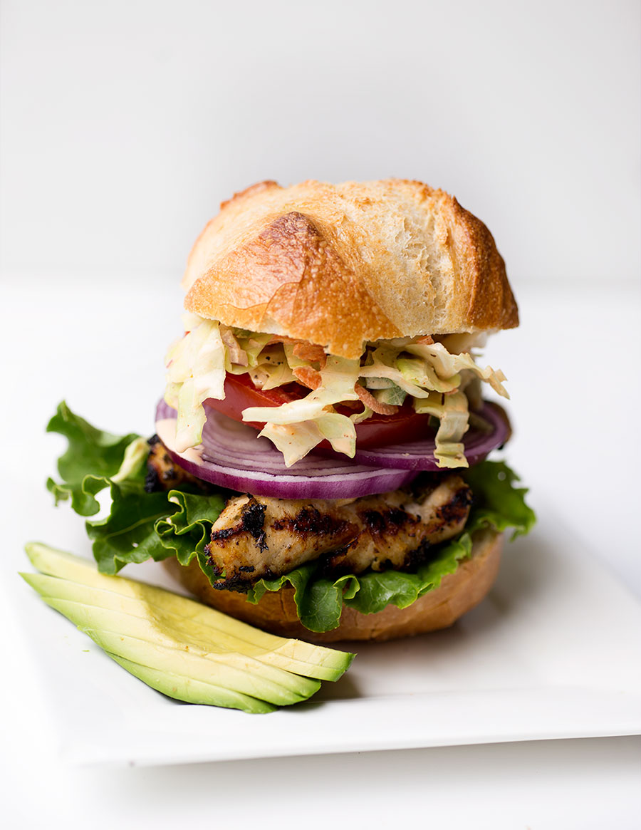 Grilled Chicken Sandwich with Spicy Coleslaw: Lemon-marinated chicken tenders stacked with a spicy cabbage slaw and finished off with a pickle and mayo dressing!