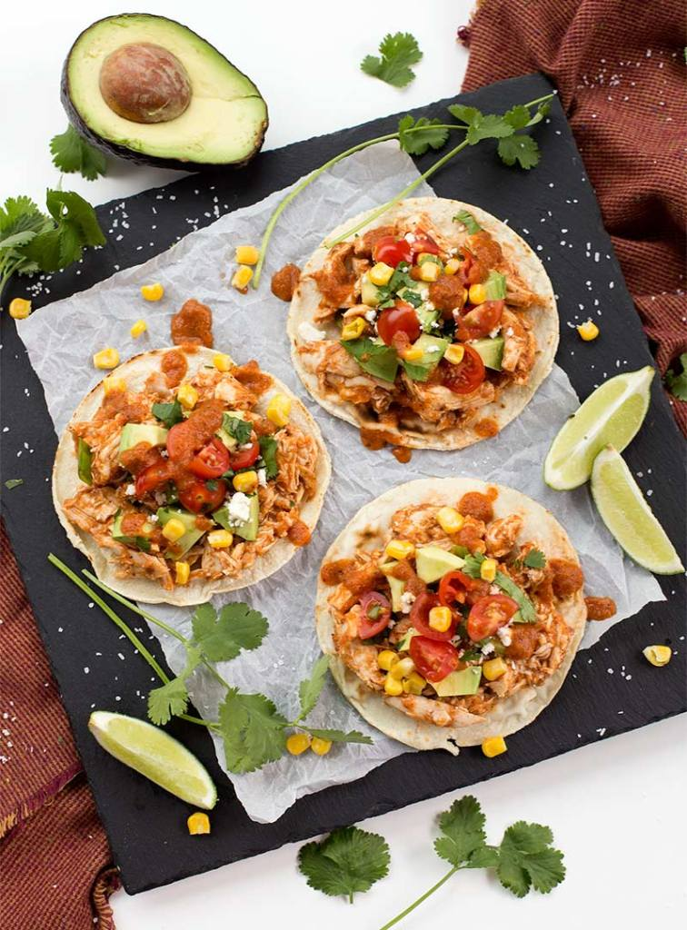 Chicken Tinga Tostadas: Cooked chicken tossed with smoky, spicy Mexican tomato sauce on a corn tortilla, finished with all your favorite Mexican toppings.