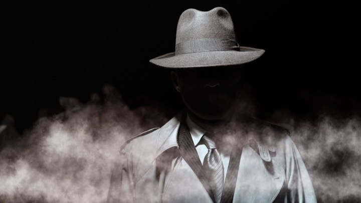 Man in the dark with a fedora hat and a trench coat, film noir style character, walking through the fog image.