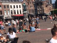 oogcontact op plein met gevulde terrassen op achter- en voorgrond 6 personen in cirkel telkens 2 tegenover elkaar