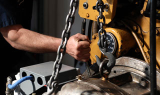 mechanic lifting transmission to repair
