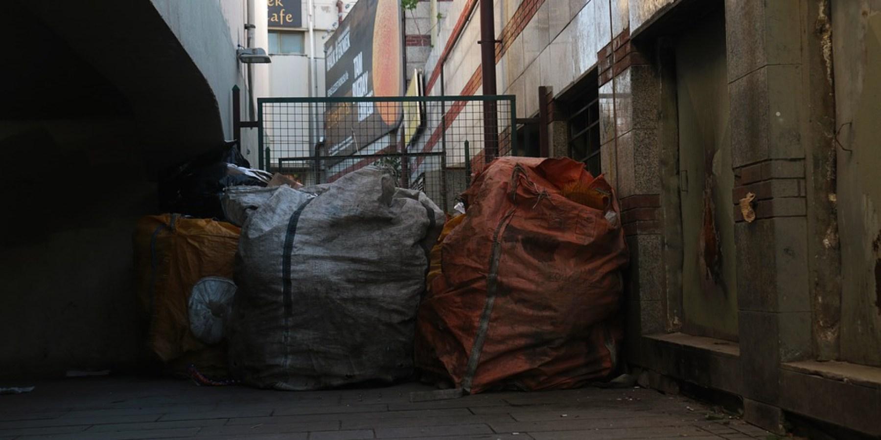 Türen von Obdachlosenunterkunft mit Müllcontainern versperrt
