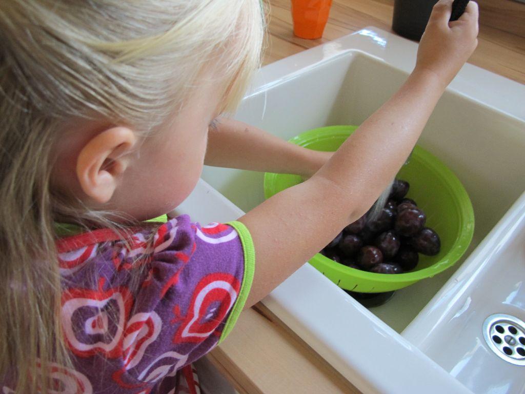 Mädchen wäscht Zwetschgen