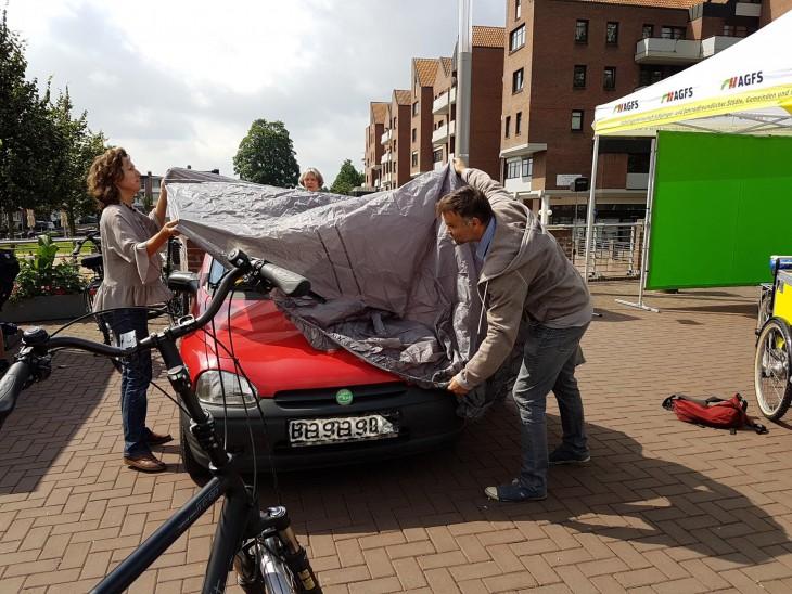 Weg damit! Pascale van Koeverden (Stadt Kleve), Wiltrud Schnütgen und Ralf Daute verhüllen das Auto von Schnütgen