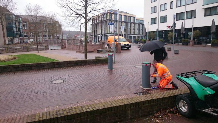 Inbus-Schlüssel griffbereit, der Regenschirm des Kollegen verhindert, dass Herr Bosch (knieend) und die sensible Elektronik Schaden nehmen (Foto: Marek Daute)