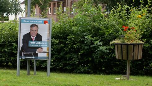 Optisches Pingpong: Links Wahlplakat vom Sozialverein, rechts Blumenkübel vom Heimatverein