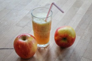 Glas mit Apfelshake und zwei Äpfel auf einem Tisch
