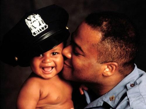 Tierna fotografia de policia besandose a su bebe sonriente