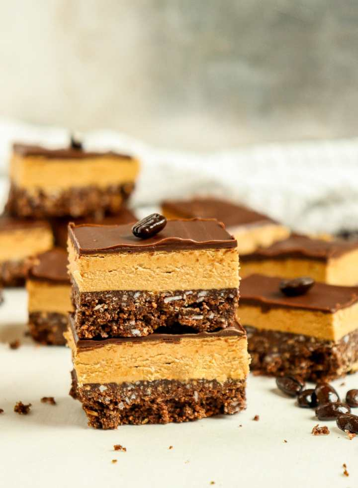 a stack of dessert bars surrounded by coffee beans