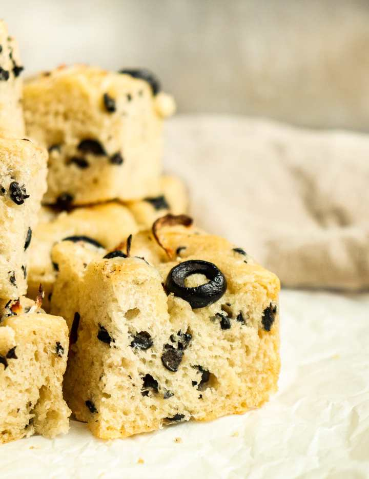 piece of focaccia bread with black olives and shallots