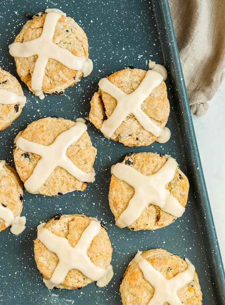 pastries topped with cross-shaped icing on a baking sheet