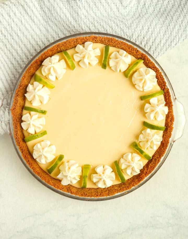 key lime pie topped with whipped cream and lime slices