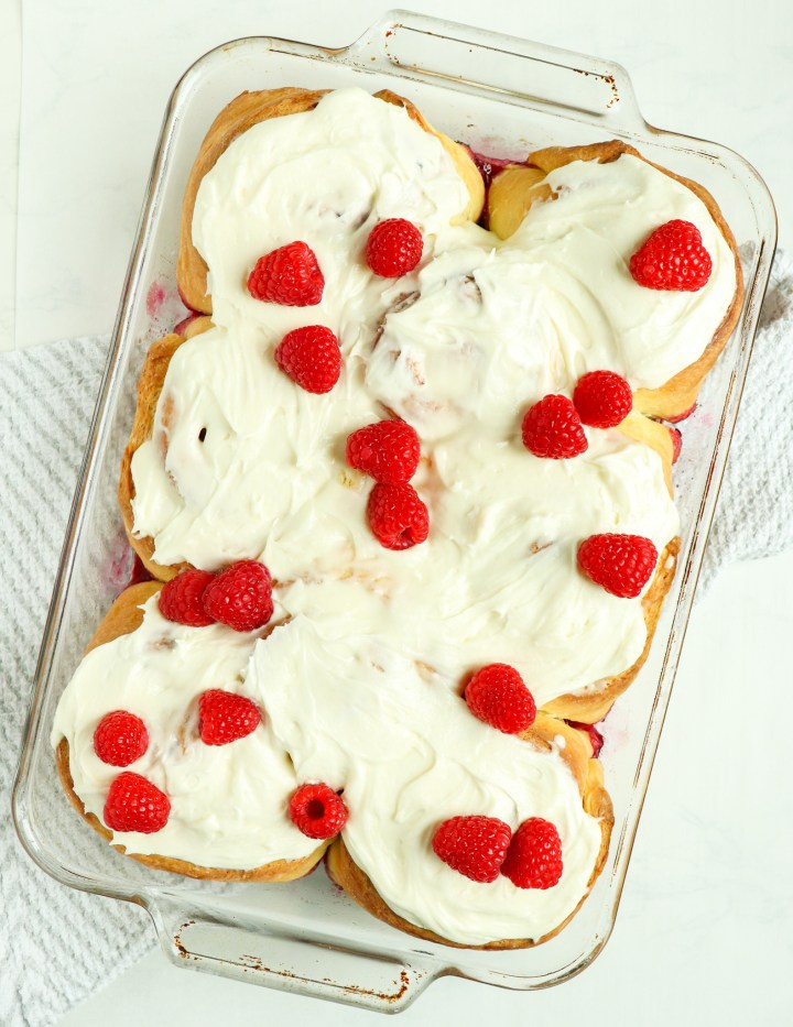 raspberry sweet rolls topped with frosting and raspberries