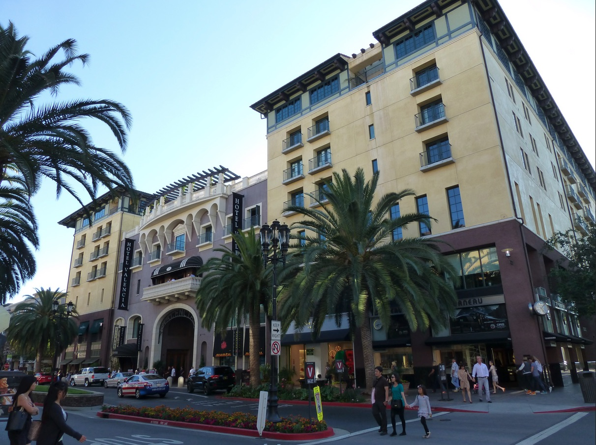 Photo of buildings and people including the hotel valencia in downtown San Jose.
