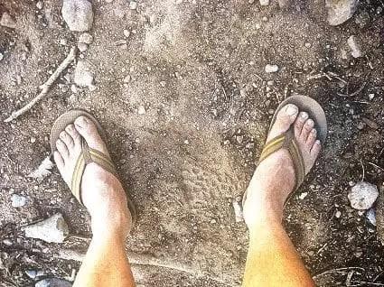 dusty feet in flip-flops on a dusty road