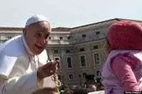 Pope Francis holding rosary with little girl close by