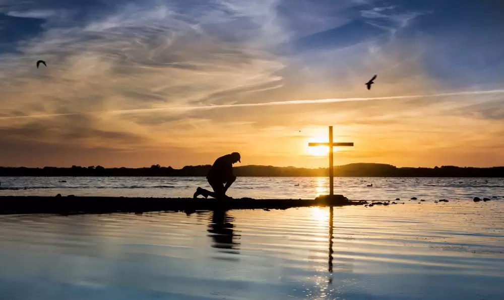 Silhouette of man kneeling in front of cross near body of water at sunset