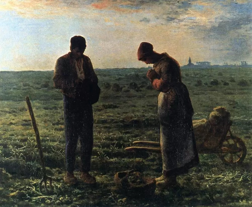 Couple in the fields bowing their heads and praying