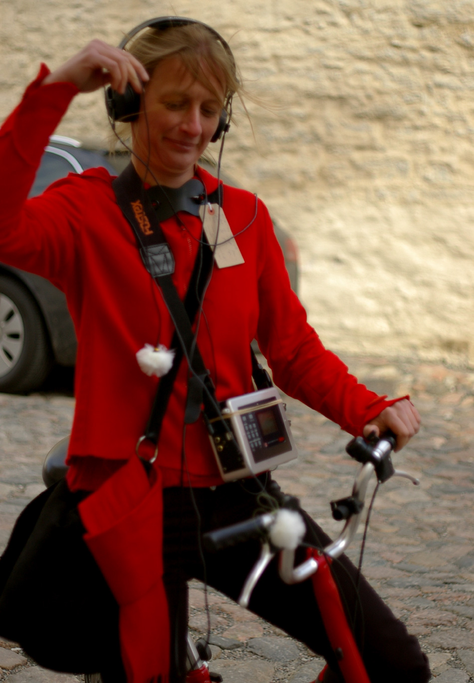 Kadrianna in her little red jacket on her little red bicycle, attempting to capture or record the sounds of cycling through Tallinn on the cobblestones with which she associates this favourite garment