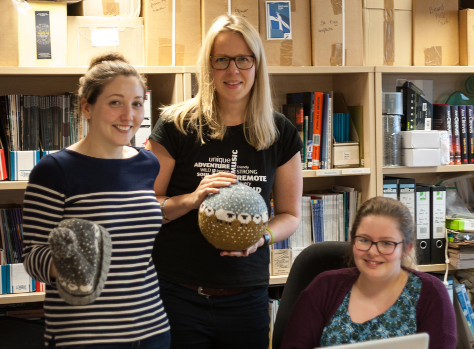 Kirsty Farquhar, Misa Hay and Selina May-Miller - team Shetland Wool Week, 2015, holding Donna Smith's Baa-ble hat and Baa-ble