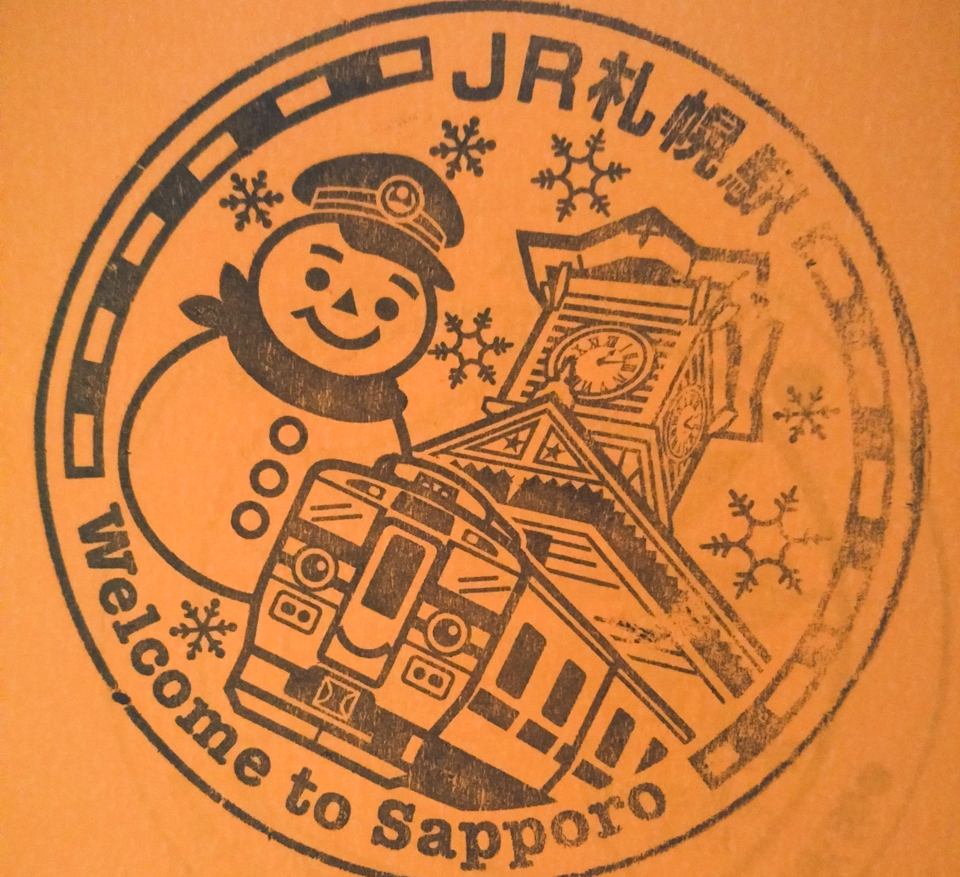 Welcome to Sapporo - the JR rubber stamp, featuring the famous clock tower, a snowman, snowflakes, and a JR train