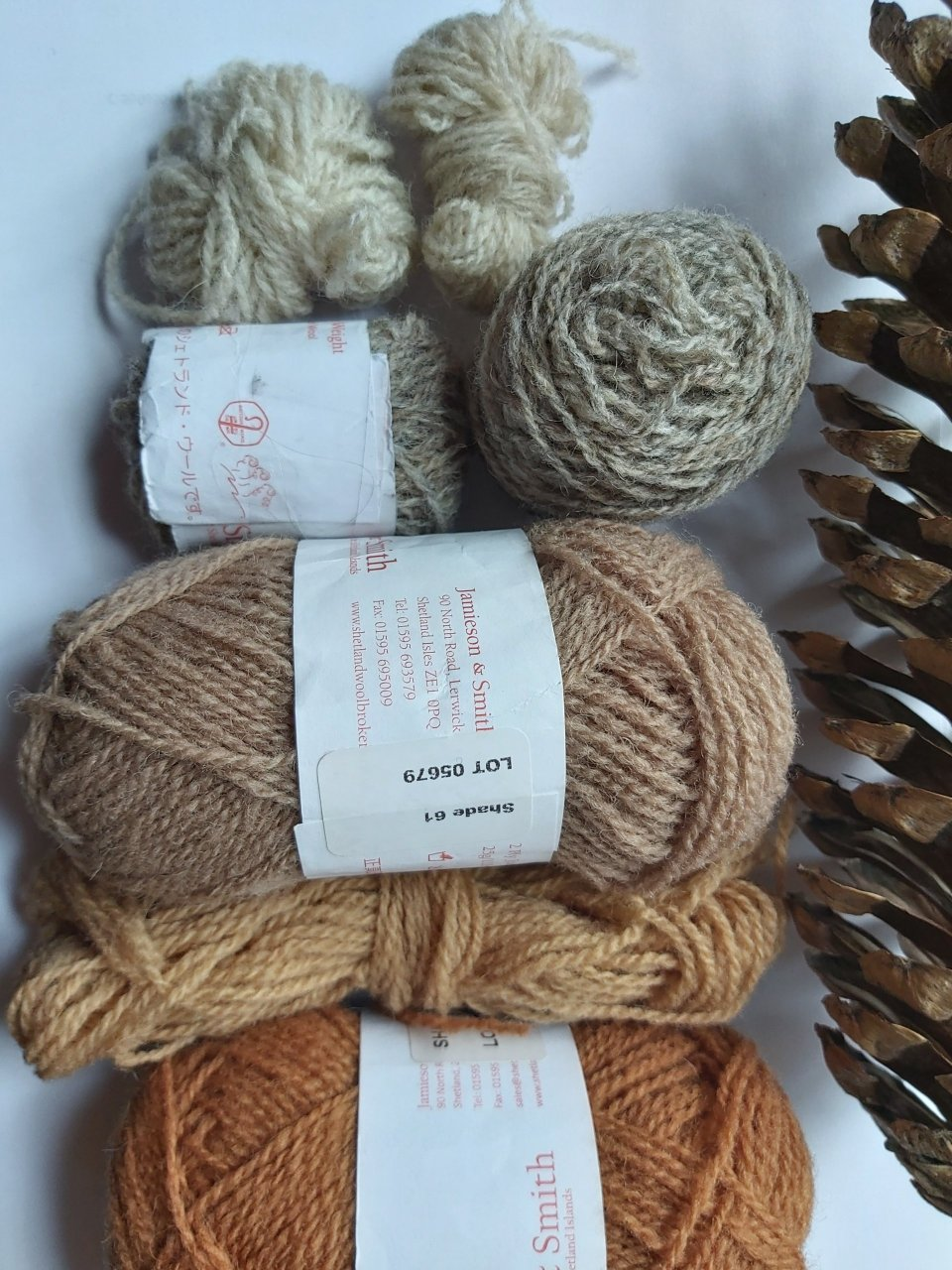 Pinecone pictured beside paler shades of yarn sequenced from top to bottom, 202, 2, 61, FC45 and 32