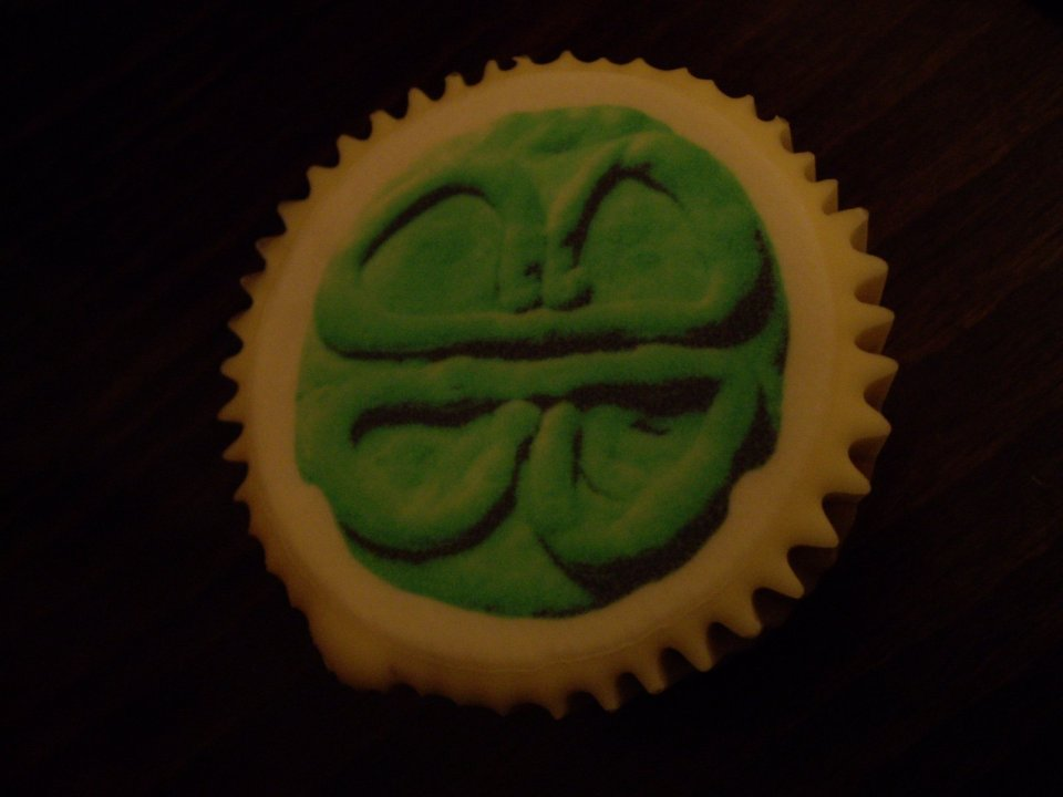 Commemorative cupcake featuring Bobby Baker's Breast Pizza motif printed on icing in green and black shades