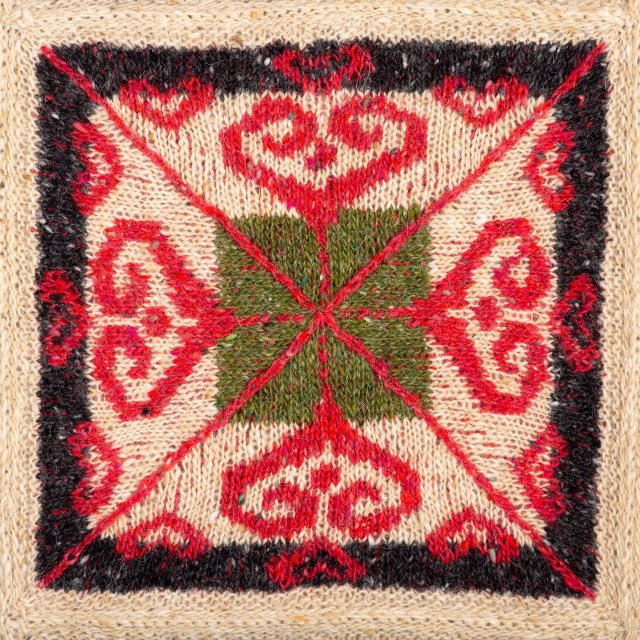 a knitted square featuring a swirly red heart motif against a background of black, beige and green