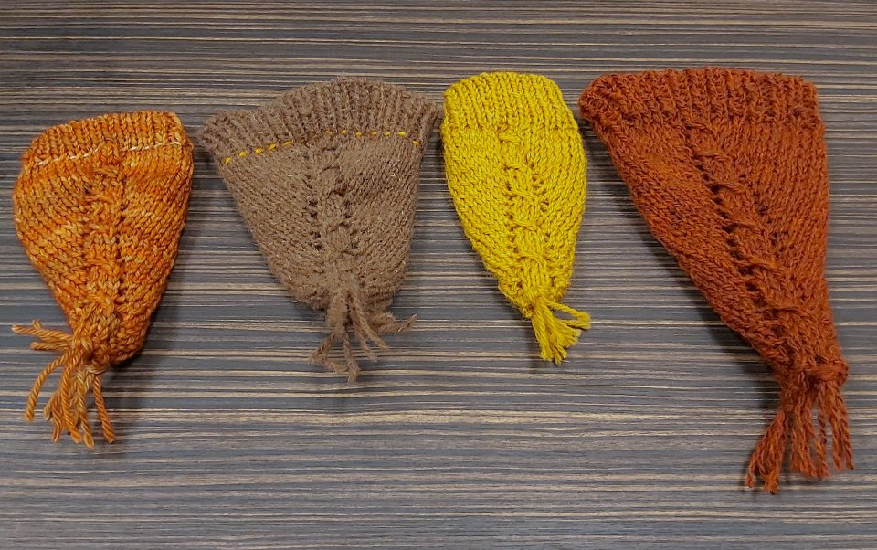 A row of miniature Hatdanas - little cones of knitting with cable detailing, yarn overs and a ribbed band at the top
