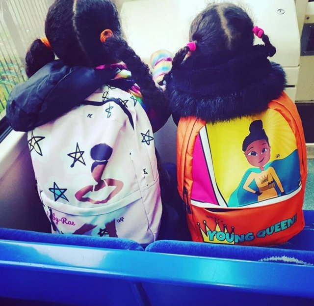 Two black girls on the bus, each wearing a rucksack featuring positive, uplifting representations of black women. One is a ballet dancer, the other is a superhero; these are Nichola's designs, printed onto schoolbags