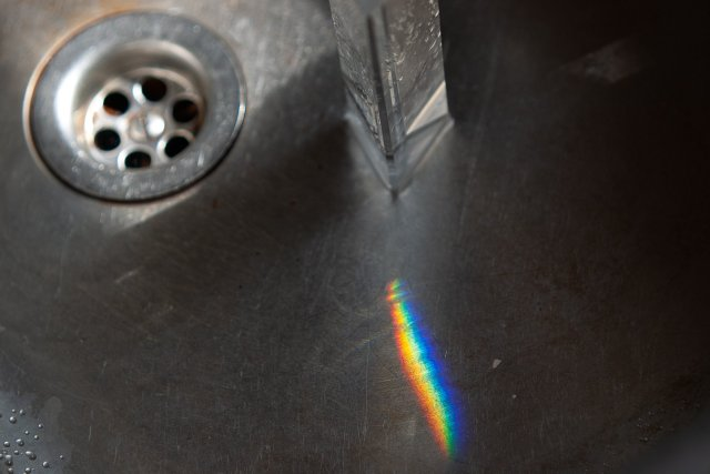 A prism in the sink, making a little rainbow on the metal