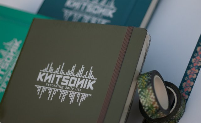 KNITSONIK Bullet Journal - in army green, with pacific green and emerald options shown in the background and a roll of dandelion washi tape, co-ordinated, to the side