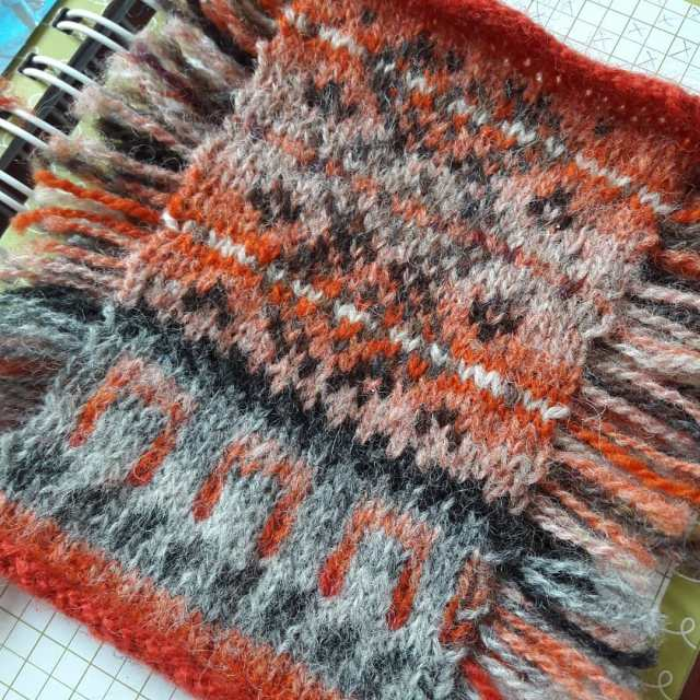 a stranded colourwork knitted postcard, the shapes and patterns of which are based on music and/or inspired by the shapes and details of a componium. Knitted and designed by Muriel Pensivy.