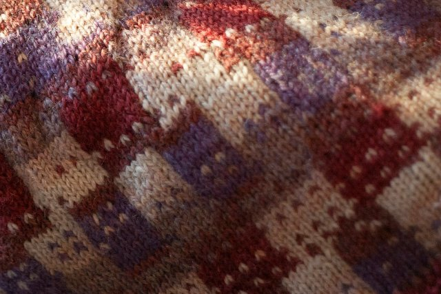 Closeup of a fabric featuring a kind of checkerboard of patterns and shapes, in a wild mix of mauves, burgundy shades, and off-white pearly creams.