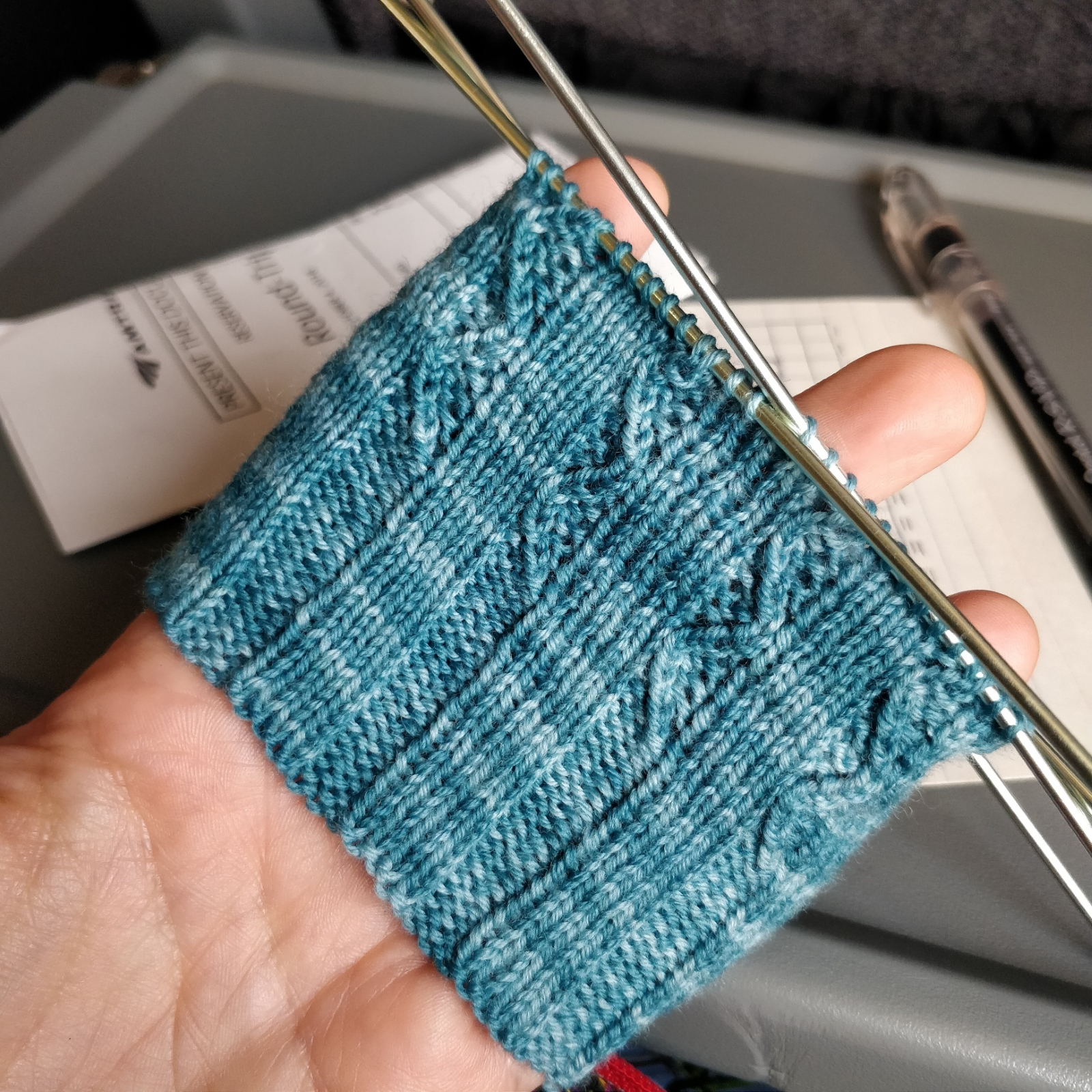 The start of a blue sock, showing a ribbed cuff and the beginning of a wavy stitch pattern.