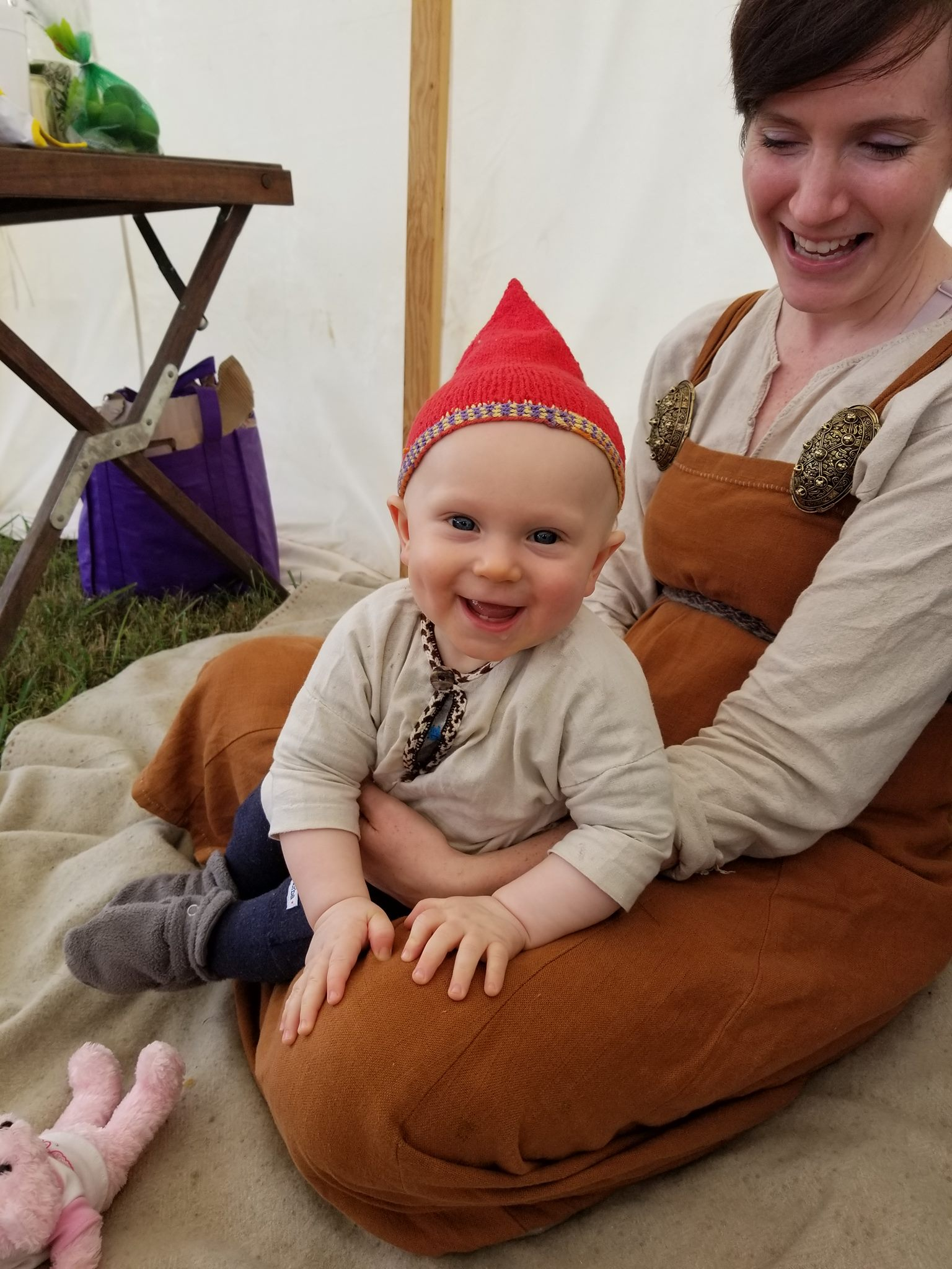 A baby wearing a bright red pointy hat smiles at the camera.