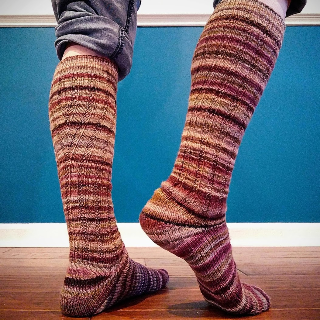 A striped pair of handspun, handknit knee socks with calf shaping.